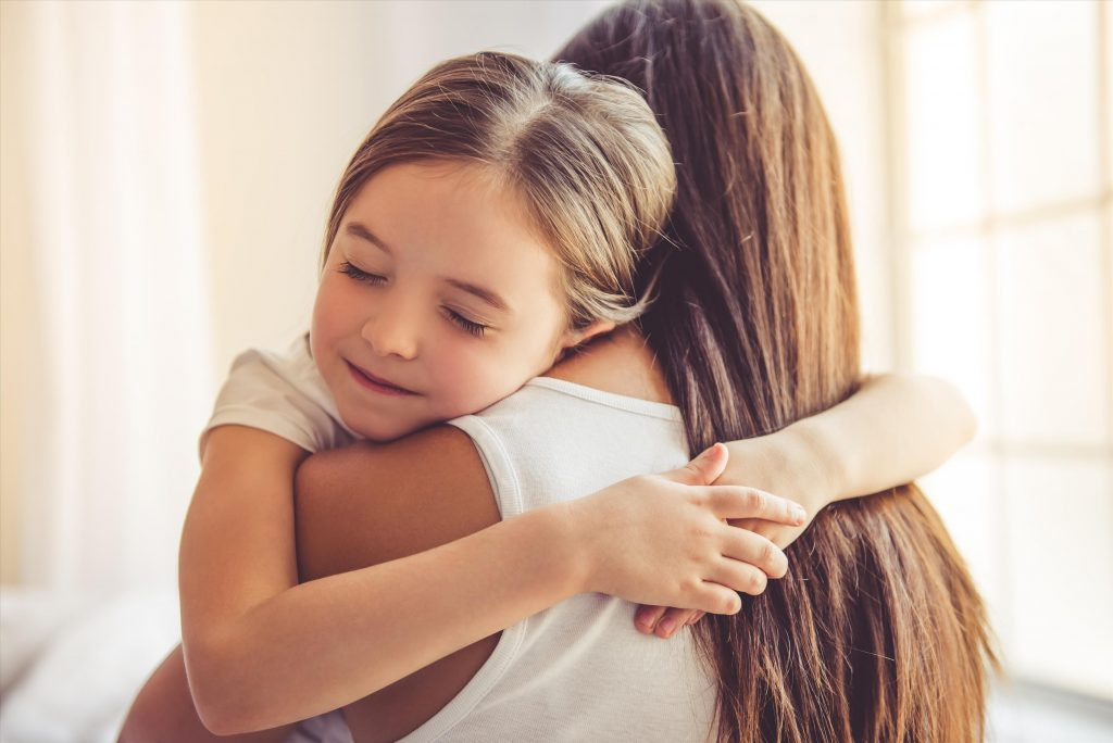 young girl hugging mum